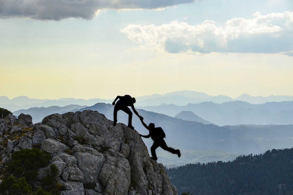 One Person Helping Another To Top Of Mountain. Representing Helping Someone Reach Their Goals